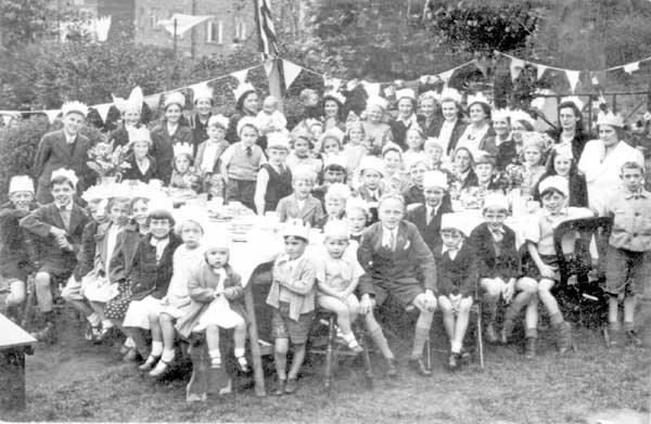 An old picture that show lots families around a table with big smile, with bunting hanging in the background.