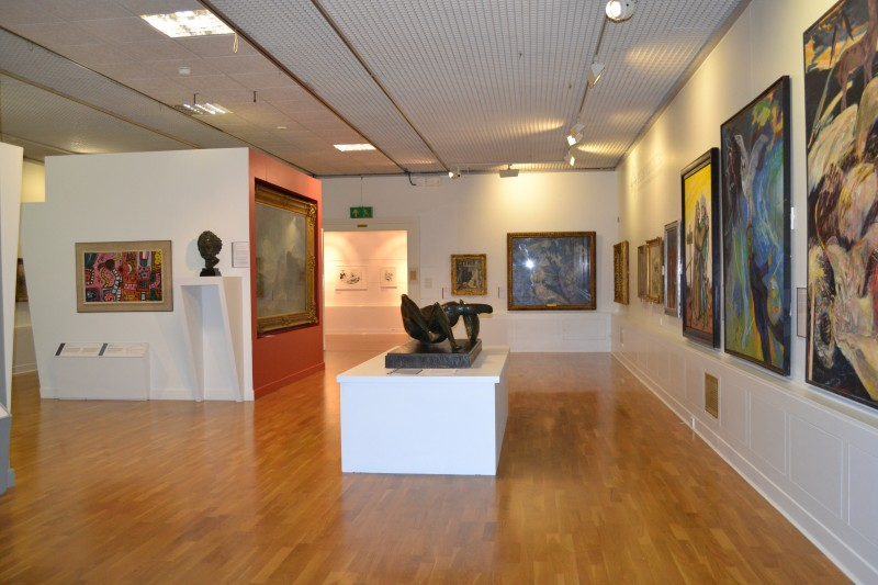 An interior of an art gallery, with spacious wooden floors interspersed with artistic creations