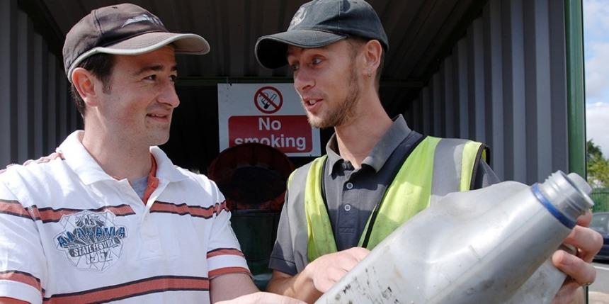 Men discussing bottle at HWRC - Tip Permits