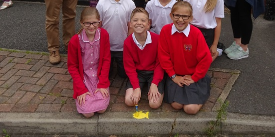 children painting a yellow fish on the kerbstone